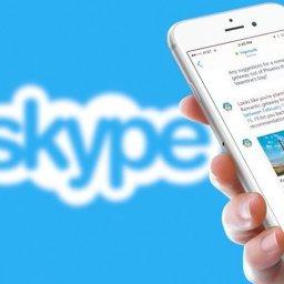 Mulher segurando smartphone com Skype, marca do aplicativo ao fundo