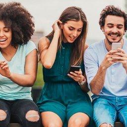 Cinco jovens diferentes usando smartphones