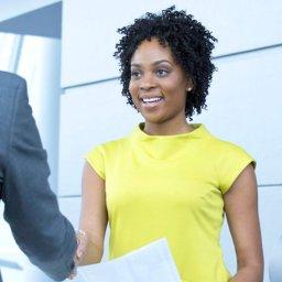 Mulher apertando a mão de um homem após reunião