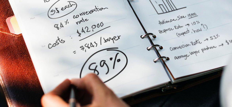 Pessoa fazendo cálculos e anotações de marketing