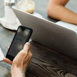 Duas pessoas em uma reunião numa cafeteria, com smartphones e notebook